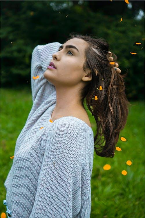 Dreamy woman standing in green field