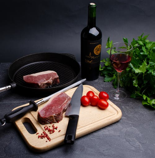 Raw meat steaks with parsley tomato and wine
