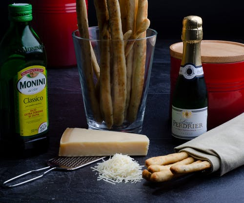 Ingredients for cooking including vine cheese and bread sticks