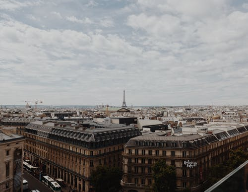 High angle of aged buildings of old Paris with Eiffel Tower at distance under cloudy sky