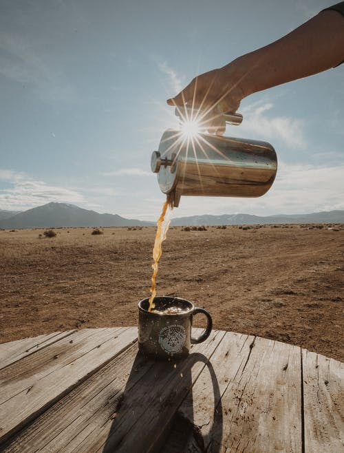 Pouring Coffee Outside Early in the Morning