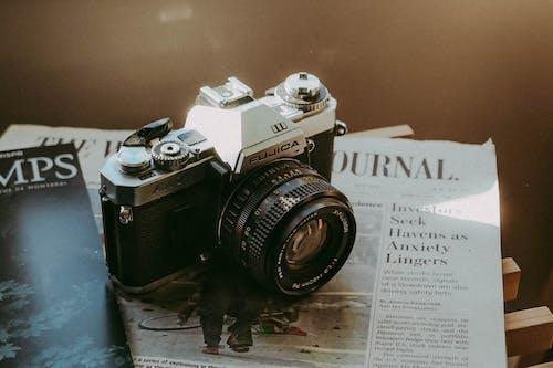 Black and Silver Nikon Dslr Camera on White Printer Paper