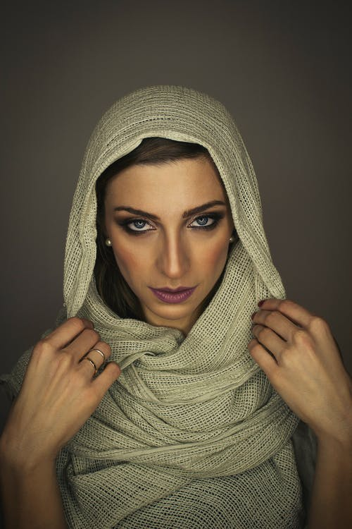 Woman in Gray Hijab Covering Her Face With Gray Textile