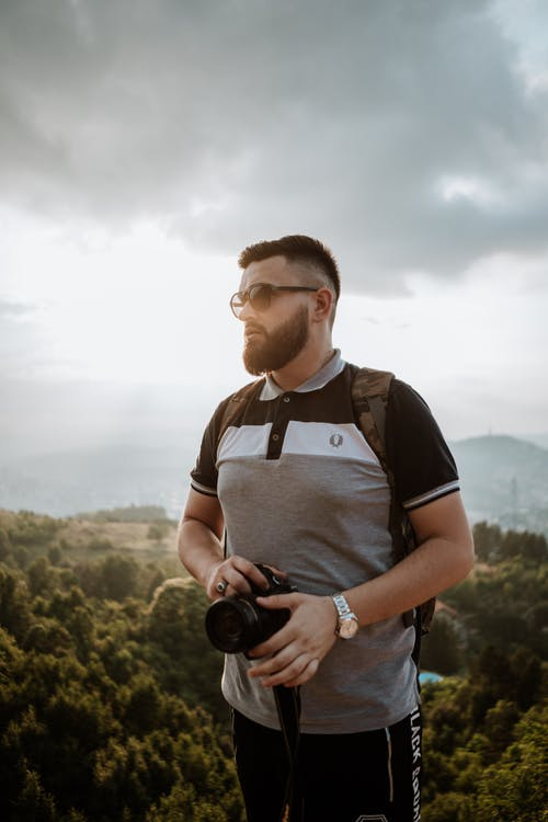 Bearded male traveler wearing casual clothes and eyeglasses with photo camera standing against woodland