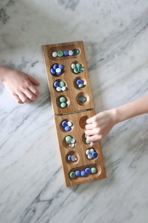 Person Holding Brown Wooden Board Game