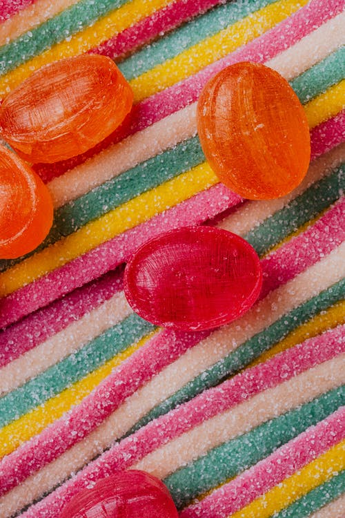 Bright caramel sweets scattered on colorful jelly candy background in confectionery