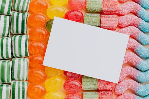 Empty paper placed on various multicolored candies in rows