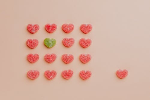 Heart shaped gummy candy assorted in rows with one candy aside against pink background
