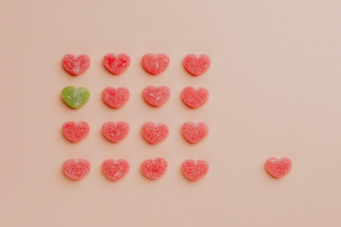 Heart shaped gumdrops on pink background