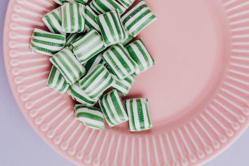 Set of delicious candies on pink plate