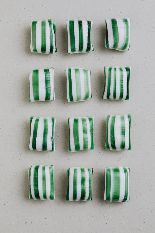 From above of sugar candies in shape of pads with green stripes laid on gray background in rows