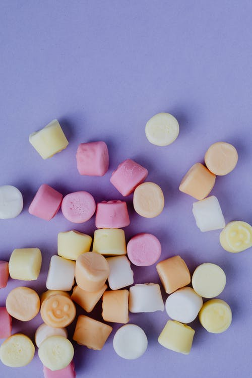 Top view of multicolored chewy candies on purple background