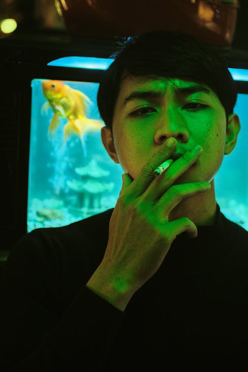 Pensive Asian man smoking cigarette at night