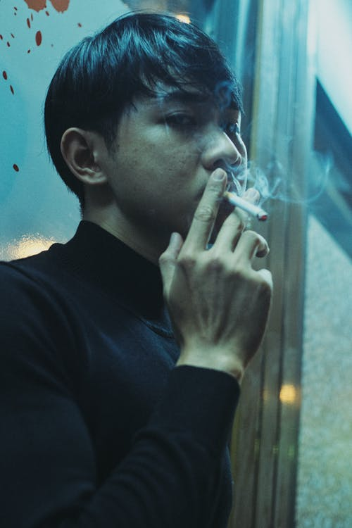 Calm ethnic guy exhaling smoke from cigarette