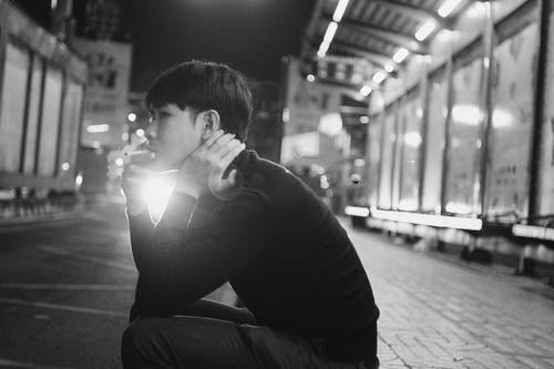 Black and white young ethnic man sitting on pavement and smoking cigarette in evening in city