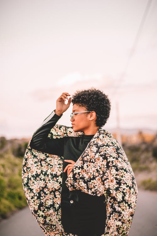 Side view of young ethnic female with short curly hair in eyeglasses wearing black outfit and covered in flowery scarf