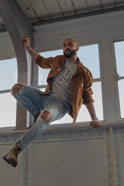 Man in Brown Leather Jacket and Blue Denim Jeans Sitting on White Wooden Window