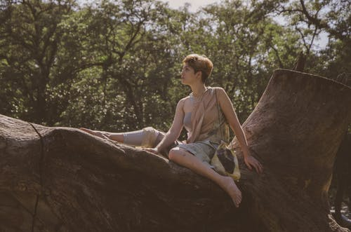 Woman Sitting on Tree Trunk