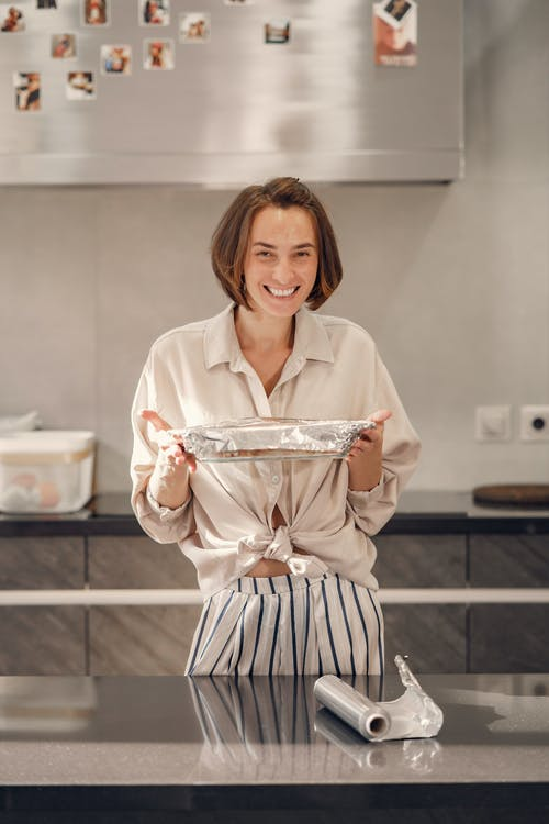 Happy Woman Holding a Baked Dish