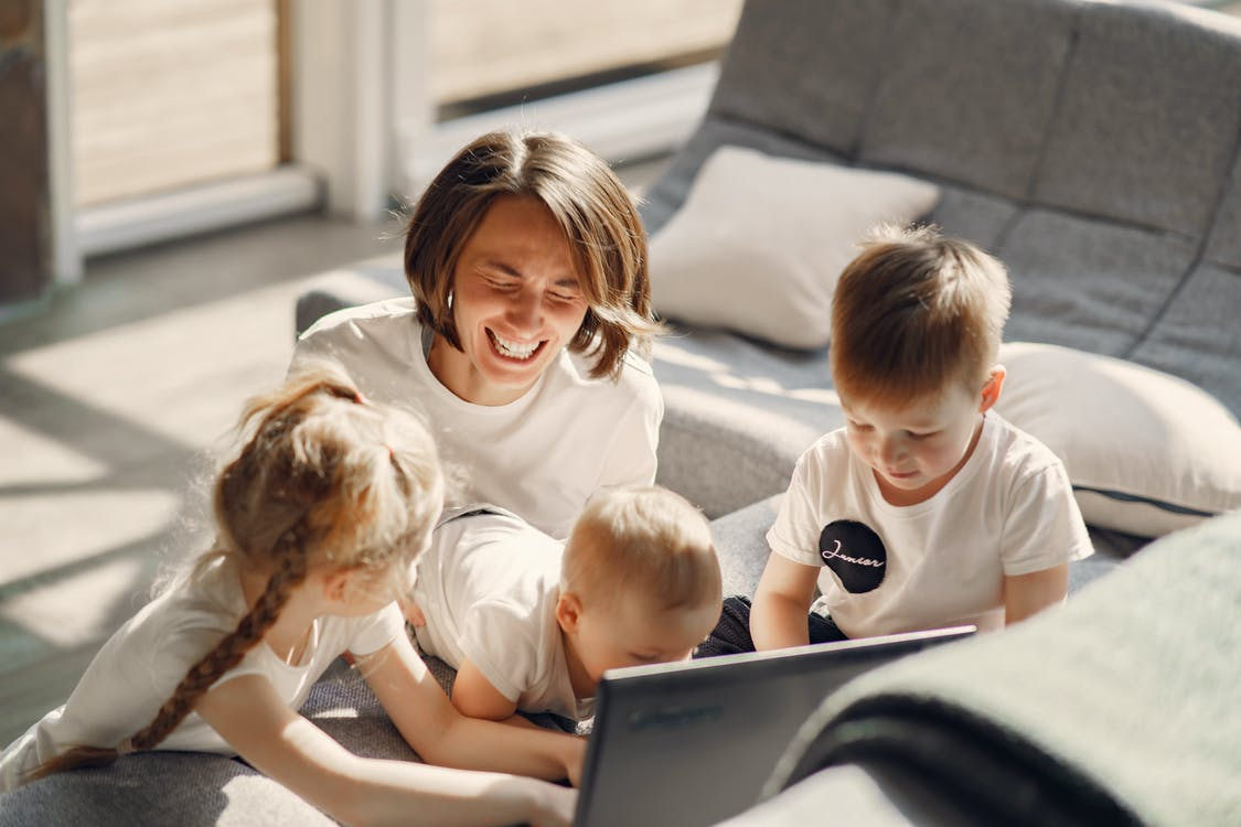 From above of cheerful woman laughing while playing with children while sitting on sofa in well lit living room