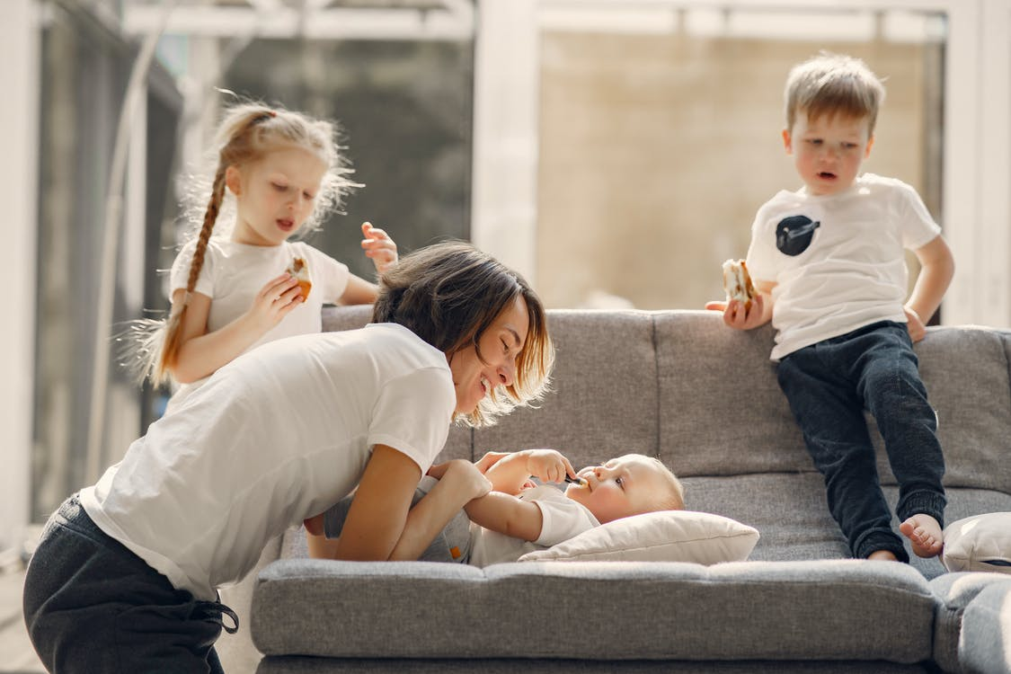 Happy mother playing with children at home