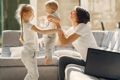 Side view of smiling woman playing with toddler boy and girl while sitting on sofa in living room