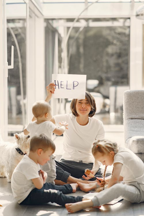 Tired mother asking for help while sitting with children