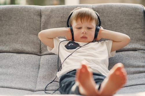 Small kid listening to music via headphones