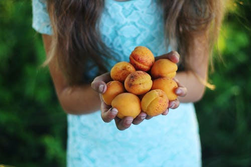 Girl Holding Yellow Round Fruits