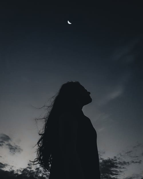 Low angle side view of silhouette of serene long haired female standing alone under night sky with moon
