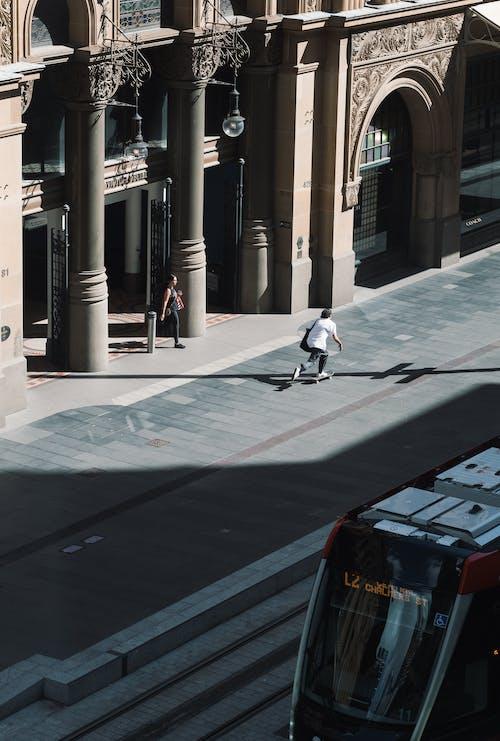 Man in White Shirt and Black Pants Skateboarding on Sidewalk