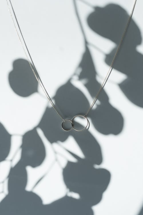 Silver Necklace on White Surface with Shadow