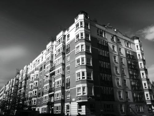 Grayscale Photo of Building Under Clear Day Sky