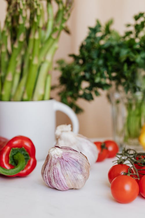 Fresh garlic with red ripe cherry tomatoes and pepper arranged near asparagus in white cup and parsley in glass on background