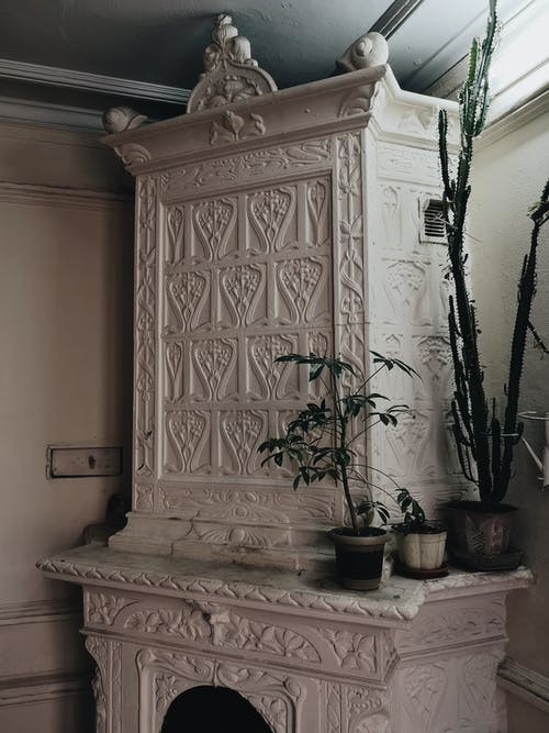 Green potted plants placed on vintage white stucco fireplace with ornamental carving in room