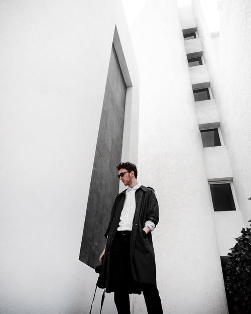 Man In Black Coat Standing Beside White Wall