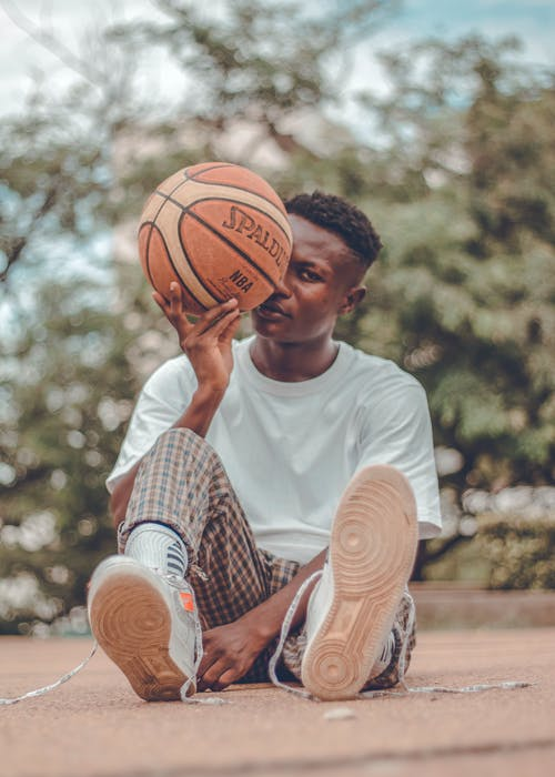 Man In White Crew Neck T-shirt Holding A Basketball