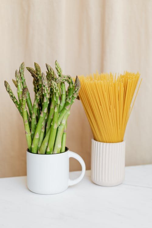 Bunches of fresh asparagus and spaghetti on table