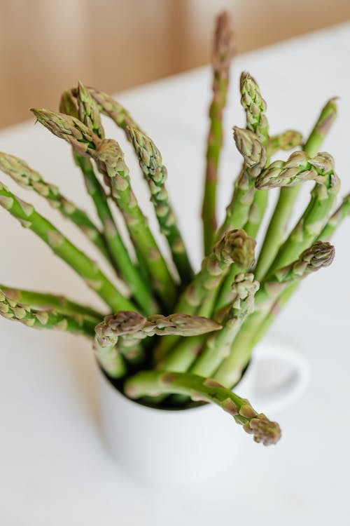 Cup with fresh green asparagus on white table