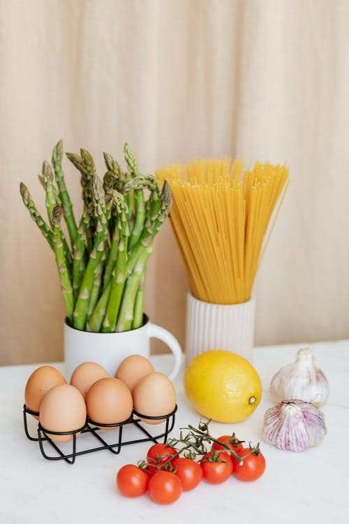 Various fresh vegetables and yellow lemon placed on white table near spaghetti in ceramic glass and raw eggs prepared for cooking pasta
