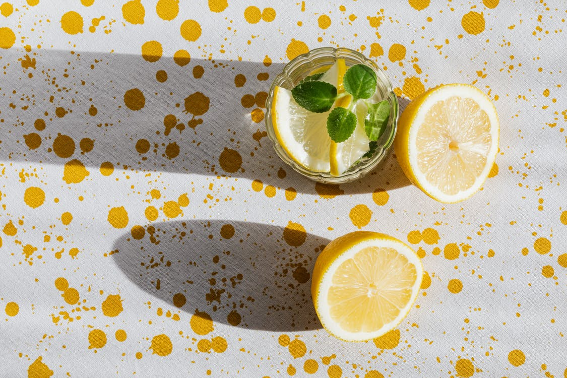 Glass of fresh cocktail and pieces of lemon