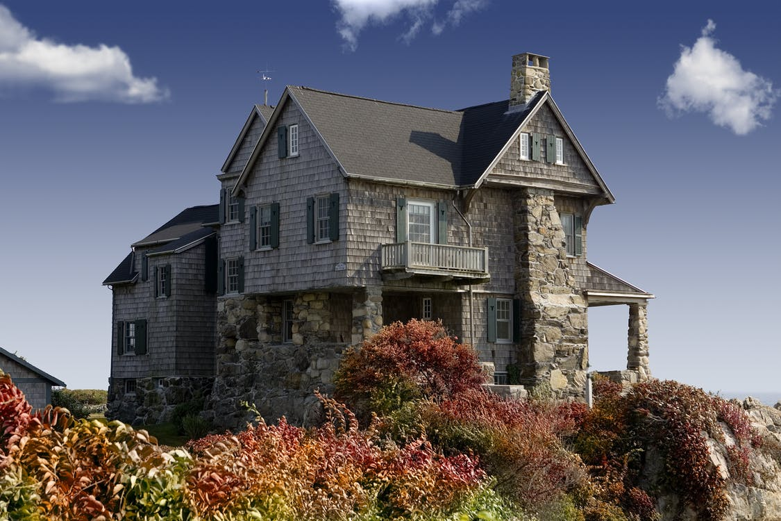 Photography of Grey Concrete House Around the Red Green Leaves Plant Under the Blue Sky