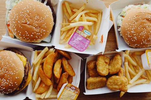 Flat lay top view of various appetizing fast food consisting of burgers and french fries