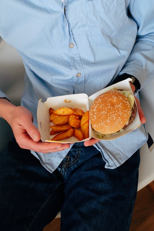 Faceless man holding box with burger and french fries