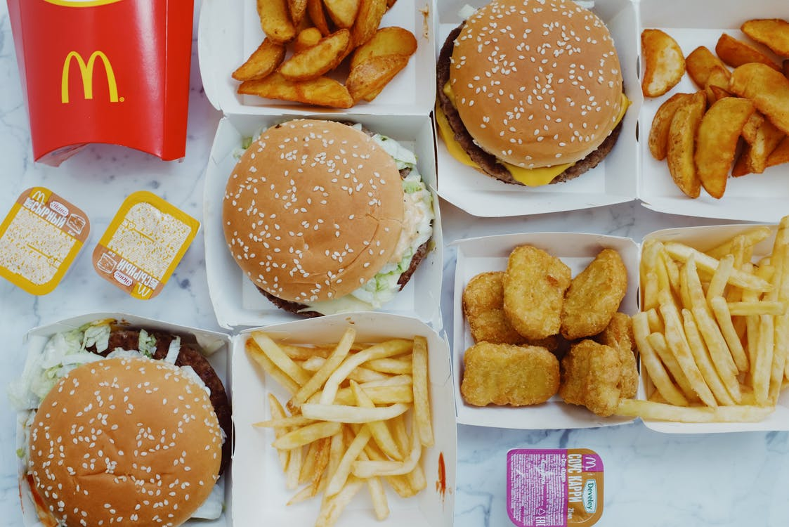 Top view flat lay of junk food including burgers with french fries and nuggets placed on marble table