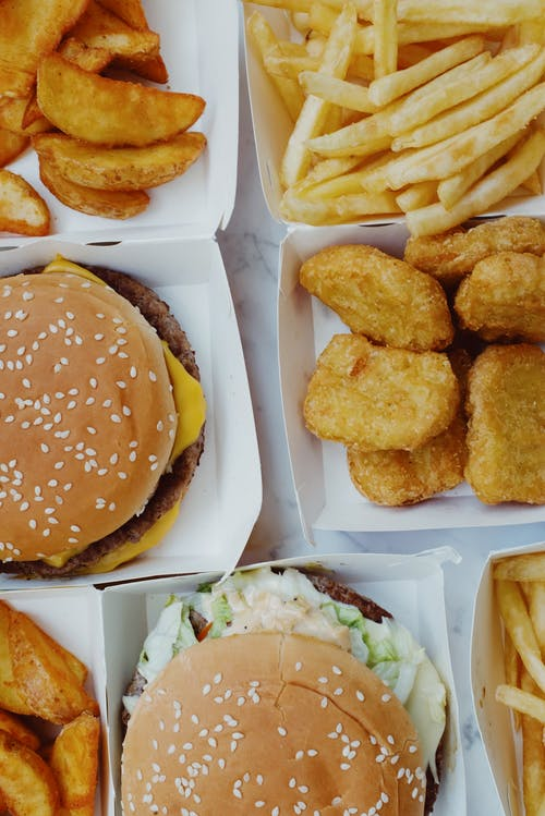Closeup of delicious junk food consisting of burgers with nuggets and french fries placed on marble table