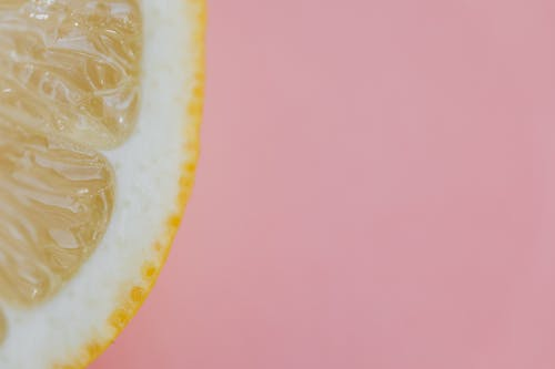 Top view flat lay composition of sliced lemon placed on pink background