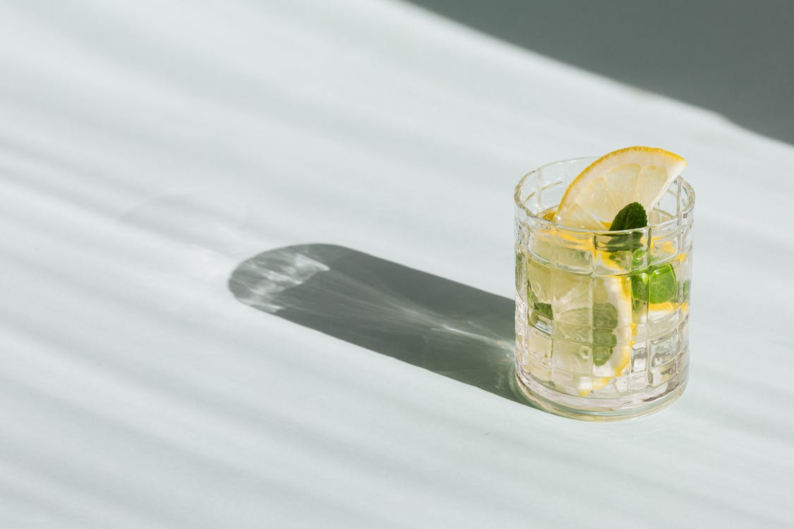 Flat lay of glass of fresh beverage with slices of lemon and leaves of mint placed on white background