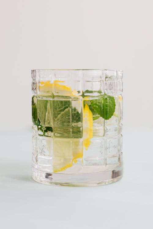 Glass of mojito with lemon and mint on white background