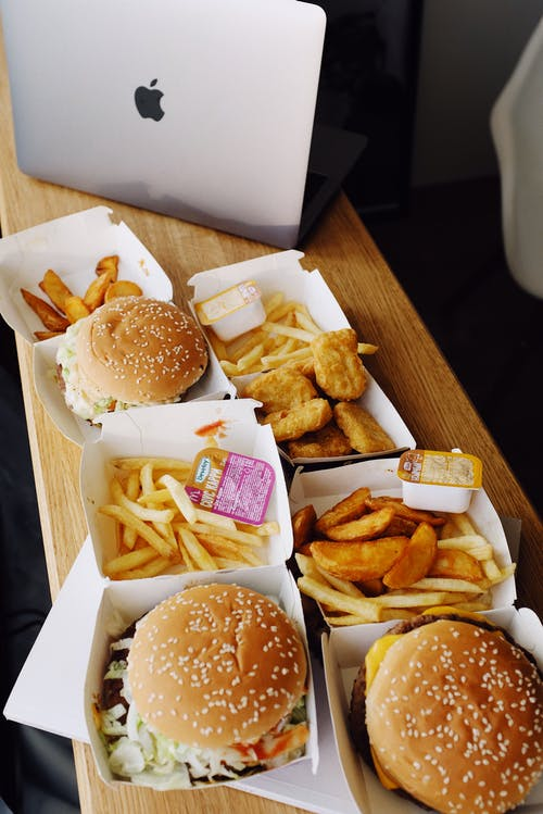 Delicious fast food and laptop on table